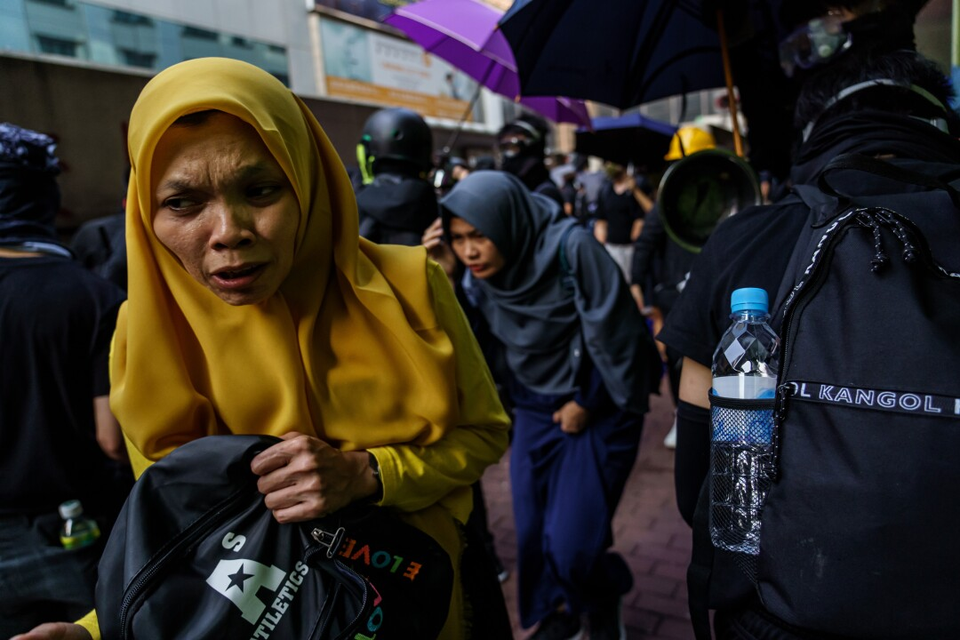 Bystanders run through crowds of demonstrators as they flee the tear gas near the Jordan district of Hong Kong.