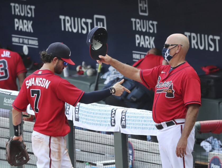 Atlanta Braves manager Brian Snitker gives Dansby Swanson and the rest of the team a tip of the cap at Truist Park after beating the New York Mets during a baseball game on Sunday, Aug. 2, 2020, in Atlanta. (Curtis Compton/Atlanta Journal-Constitution via AP)