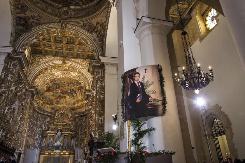 Una imagen del fallecido magistrado Rosario Livatino es exhibida durante una ceremonia de beatificación en la catedral de Agrigento, en el sur de Italia, el domingo 9 de mayo de 2021. (Fabio Peonia/LaPresse vía AP)