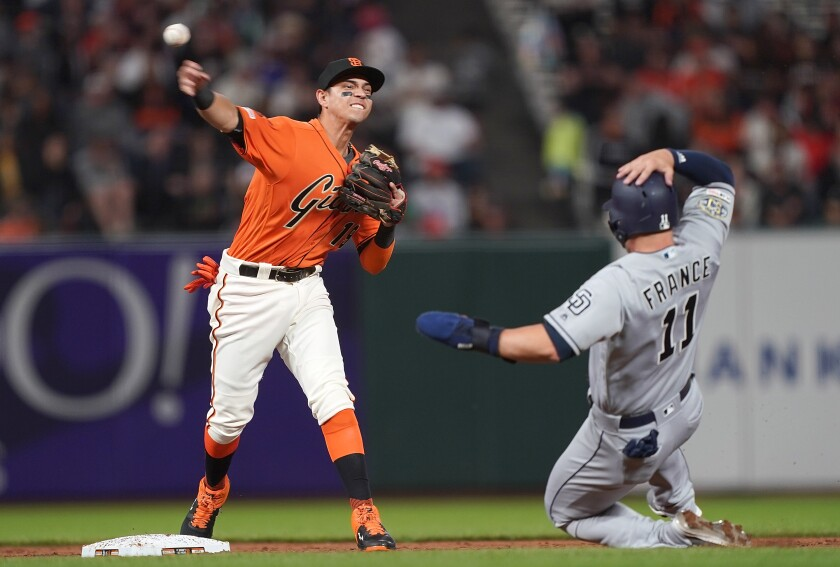 San Francisco Giants second baseman Mauricio Dubon completes a double play as the Padres' Ty France slides in the top of the second inning Friday night at Oracle Park.