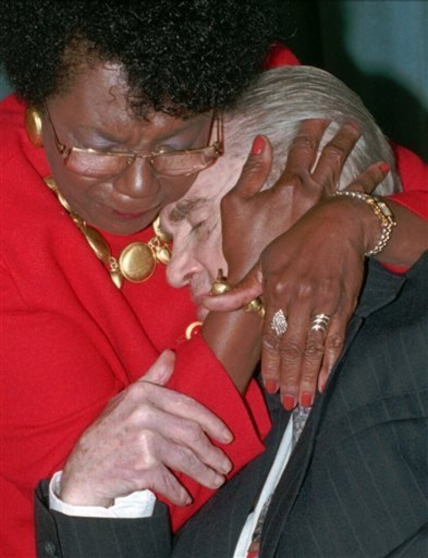 FILE - This is an Aug. 26, 1994 file photo of former four-term Alabama Gov. George C. Wallace in an emotional moment as he hugs friend Connie Harper at a celebration of Wallace's 75th birthday. Fifty years ago, Wallace stood in a doorway at the University of Alabama and tried to block two black stu