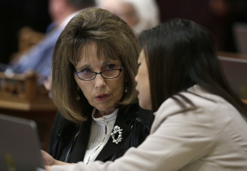 FILE - In this June 14, 2018 file photo, then-Senate Republican Leader Patricia Bates, left, of Laguna Niguel, confers with Sen. Janet Nguyen, R-Fountain Valley, in Sacramento, Calif. Bates joined other Republican state senators on Thursday, June 11, 2020, in opposing a measure that would require counties to send a ballot to every registered voter for the November election. The bill was approved and sent to the Assembly. (AP Photo/Rich Pedroncelli, File)