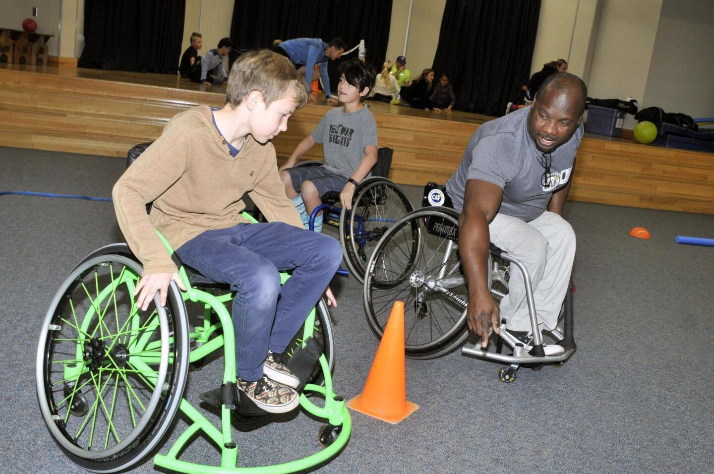 Samuel Nehemiah from the Challenged Athletes Foundation helps 4th graders navigate the obstacle course