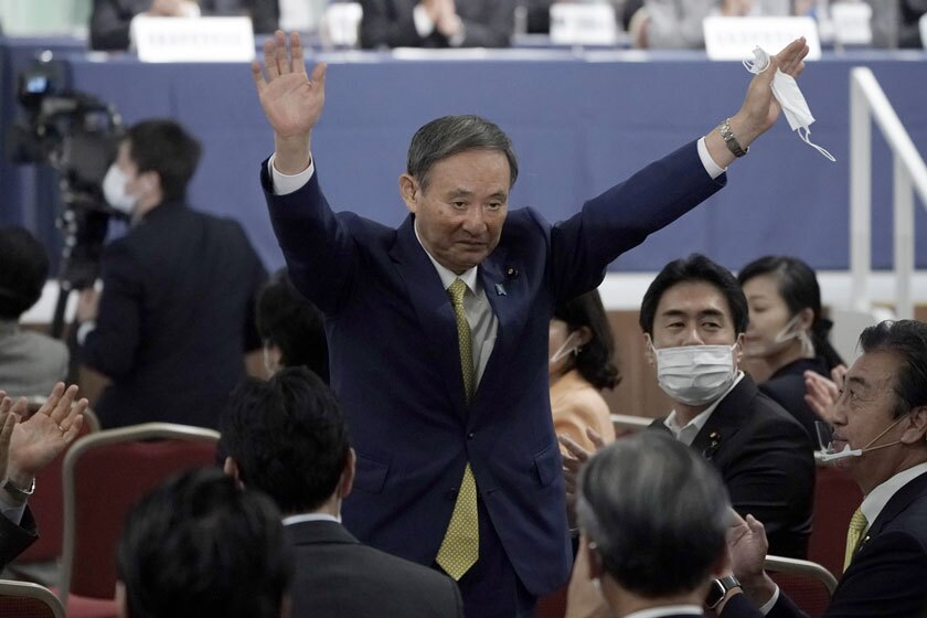 Japanese Chief Cabinet Secretary Yoshihide Suga acknowledges applause after winning a party vote on Monday.