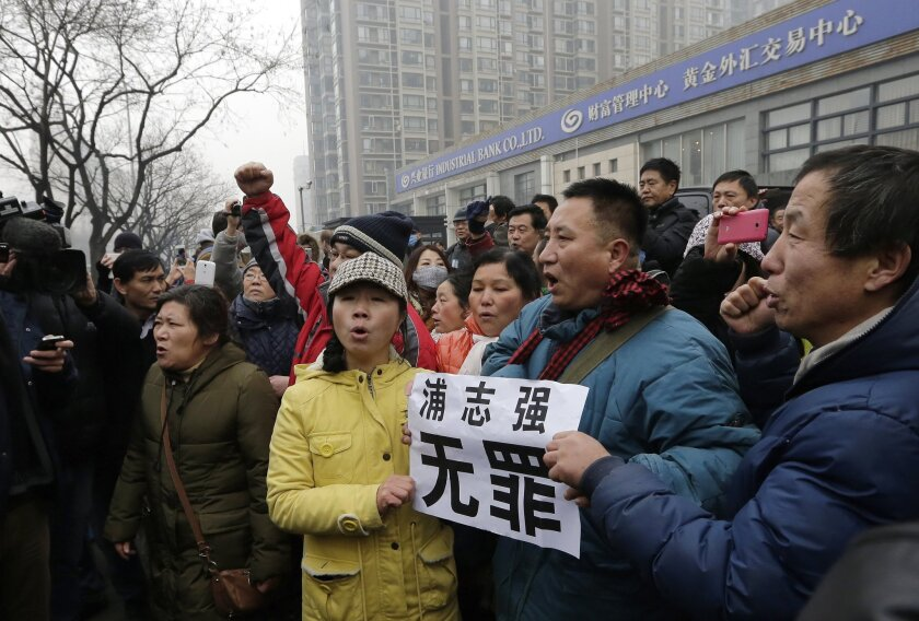 Supporters of prominent rights lawyer Pu Zhiqiang chant slogans as they gather during his trial in the Beijing Second Intermediate People's Court on Monday.