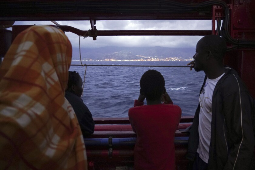Migrants look at the Italian shoreline from aboard the Ocean Viking as it approaches the Sicilian port of Messina, southern Italy, Tuesday, Sept. 24, 2019. The Ocean Viking has docked in Sicily, Italy, to disembark 182 men, women and children rescued in the Mediterranean Sea after fleeing Libya. (AP Photo/Renata Brito)