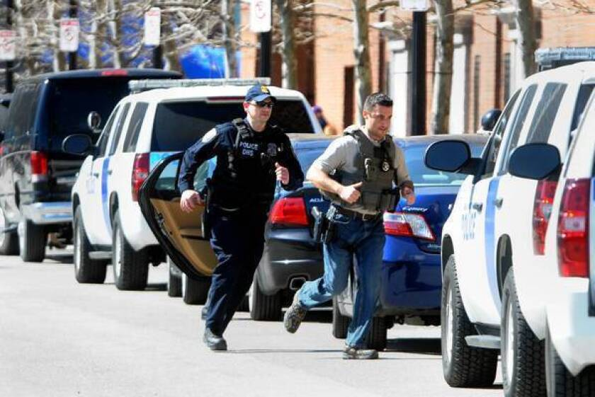 Law enforcement officials run toward the Joseph Moakley federal courthouse in Boston after a bomb threat was reported there.