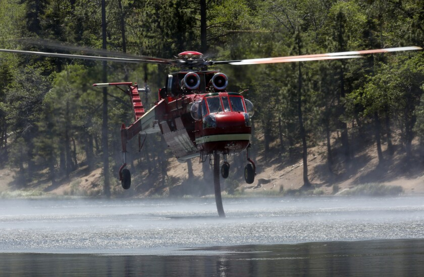 A firefighting helicopter sucks up water from Jenks Lake as it works to control flames in the Lake fire in the San Bernardino National Forest.