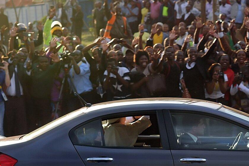 Pope Francis, riding in a Honda sedan, waves at crowds as he passes through the streets of Nairobi, Kenya, on Nov. 25.