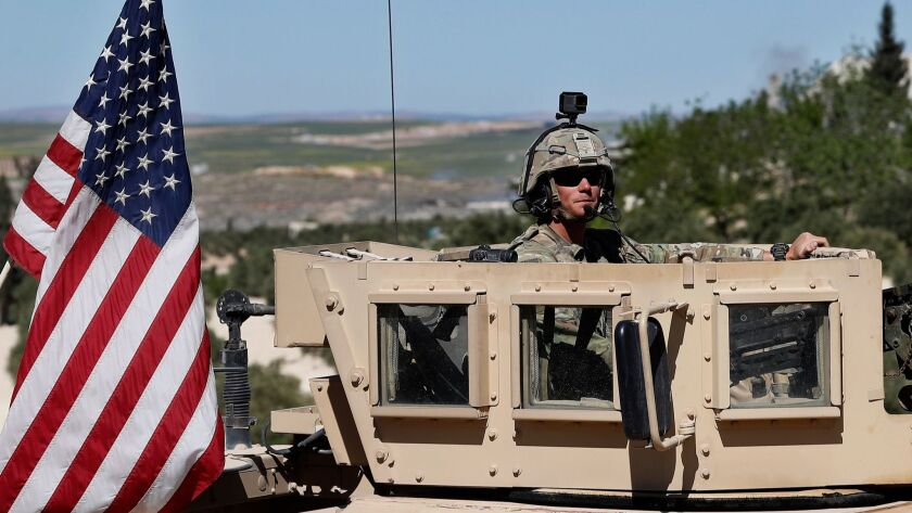 FILE - In this Wednesday, April 4, 2018 file photo, a U.S. soldier sits on his armored vehicle on a
