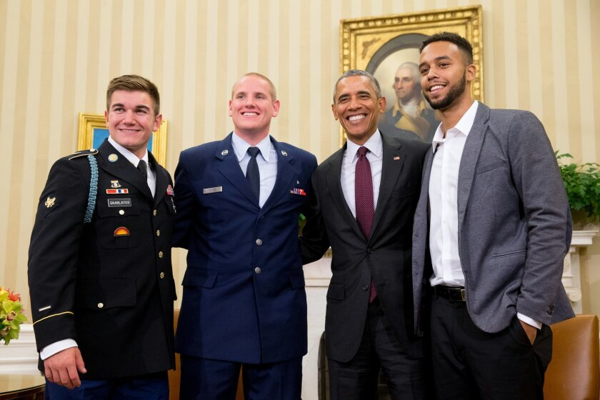 CORRECTS TO PARIS-BOUND TRAIN - President Barack Obama poses for a photograph with Oregon National Guardsman, from left, Alek Skarlatos Air Force Airman 1st Class Spencer Stone, and Anthony Sadler, in the Oval Office of the White House in Washington, Thursday, Sept. 17, 2015, to honor them for heroically subduing a gunman on a Paris-bound passenger train last month. (AP Photo/Andrew Harnik)