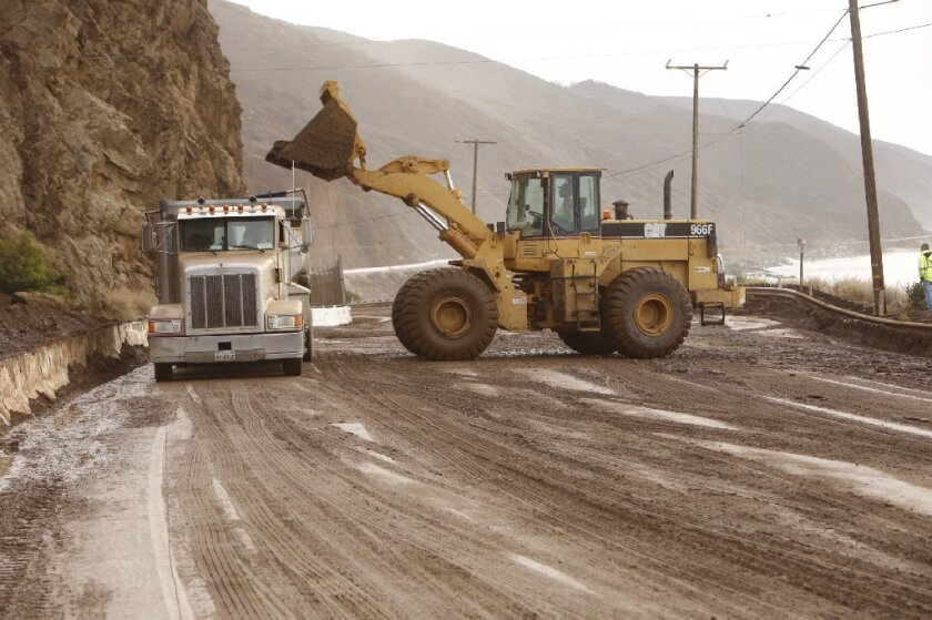 Work crews remove mud and debris earlier from a landslide that closed Pacific Coast Highway between Las Posas and Yerba Buena roads. The highway reopened on Friday.