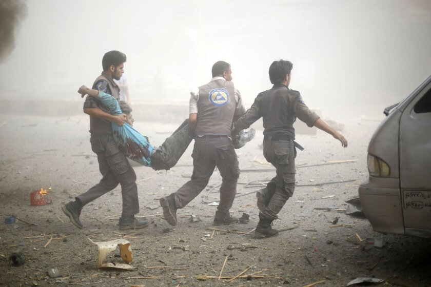 Emergency personnel carry a wounded man following airstrikes on a marketplace in a rebel-held area of Douma, Syria, on Aug. 16.