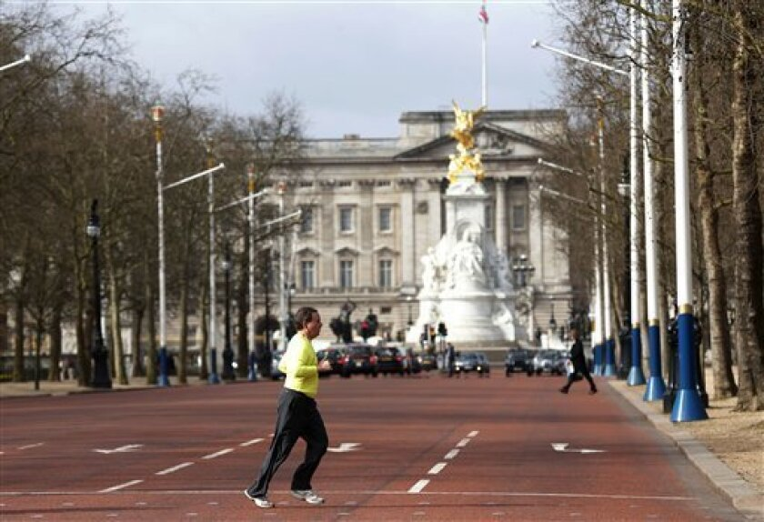 Backdropped by Buckingham Palace, a runner jogs across the Mall in London where the finish area of the forthcoming London Marathon is to be located, Tuesday, April 16, 2013. British police are reviewing security plans for Sunday's London Marathon, the next major international marathon, because of the bombs that killed three people at the marathon in Boston Monday. (AP Photo/Sang Tan)