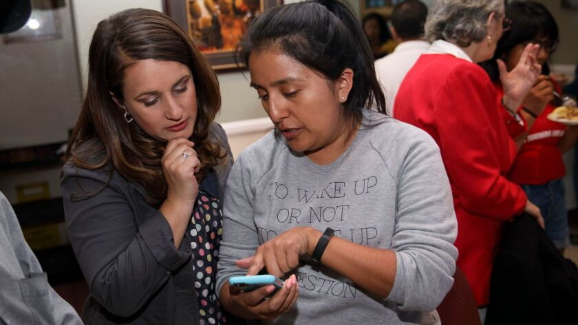 Candidate Imelda Padilla, left, looks at voting results with Gemma Jimenez during an LAUSD School Bo