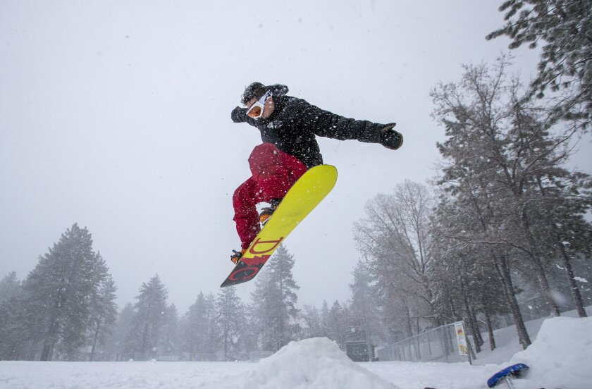 Snowboarder Malcolm Pope of Carlsbad catches air in Wrightwood, Calif., on Nov. 27. The Southland is facing another soggy holiday.