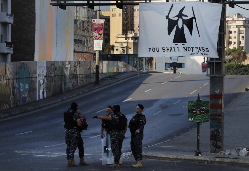 Riot police stand guard on a main highway blocked by anti-government protesters during ongoing protests against the Lebanese government in Beirut, Lebanon, Monday, Nov. 4, 2019. Protesters closed major roads in Beirut and elsewhere in Lebanon Monday, accusing political leaders of dragging their feet on the formation of a new government amid differences over who should be included. (AP Photo/Hussein Malla)