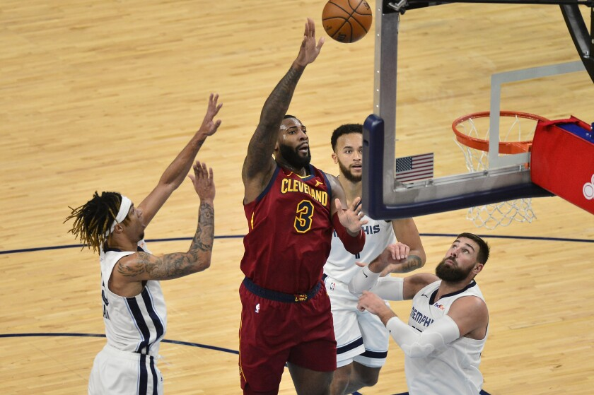 Cleveland Cavaliers center Andre Drummond (3) shoots between Memphis Grizzlies forwards Brandon Clarke, from right, and Kyle Anderson (1), and center Jonas Valanciunas (17) in the second half of an NBA basketball game Thursday, Jan. 7, 2021, in Memphis, Tenn. (AP Photo/Brandon Dill)