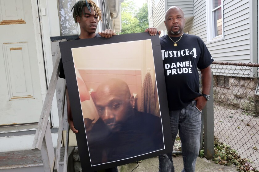 FILE — In this Sept. 3, 2020 file photo, Joe Prude, brother of Daniel Prude, right, and his son Armin, stand with a picture of Daniel Prude in Rochester, N.Y. Newly released transcripts show that a grand jury investigating the police suffocation death of Daniel Prude last year in Rochester, New York, voted 15-5 to clear the three officers involved in his restraint of a criminally negligent homicide charge sought by prosecutors. (AP Photo/Ted Shaffrey, File)