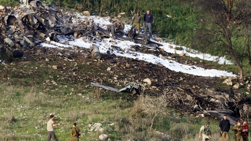 Israeli security stands around the wreckage of an F-16 that crashed in northern Israel, near kibbutz