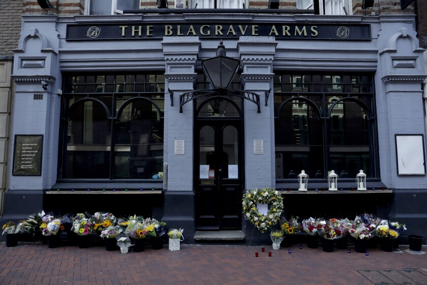 FILE - In this Tuesday, June 23, 2020 file photo, flowers are placed outside the Blagrave Arms pub near the scene of a fatal multiple stabbing attack in Forbury Gardens park, in Reading, England. A 26-year-old Libyan man pleaded guilty to murder on Wednesday, Nov. 11 for stabbing three men to death as they sat in an English city park. Khairi Saadallah admitted three counts of murder and three of attempted murder for the June 20 attack in Reading, 40 miles (64 kilometers) west of London. Friends James Furlong, David Wails and Joseph Ritchie-Bennett were enjoying a warm Saturday evening in the town's Forbury Gardens park when they were stabbed. (AP Photo/Matt Dunham, file)