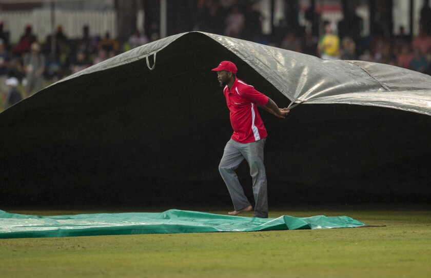A stadium worker pulls on the rain covers as play is delayed during the 2nd One Day cricket international match between South Africa and England at Kingsmead stadium in Durban, South Africa, Friday, Feb. 7, 2020. (AP Photo/Themba Hadebe)