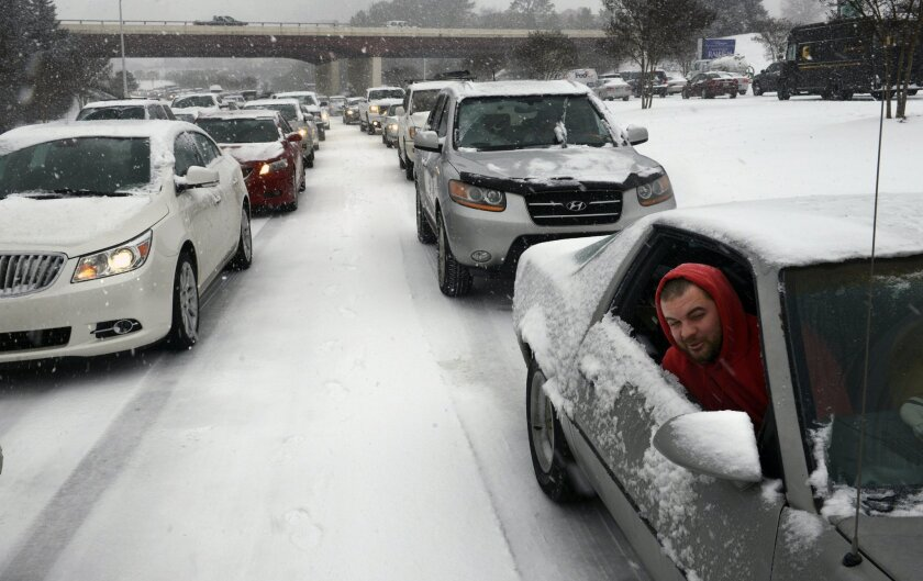 Kevin Miller looks out of the passenger window of his friend's car as they sit in stuck traffic during a winter storm Wednesday Feb. 12, 2014, in Raleigh, N.C. (AP Photo/The News & Observer, Scott Sharpe)