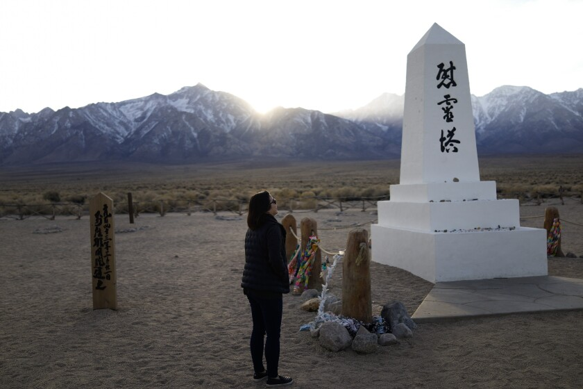 FILE - In this Feb. 17, 2020, file photo Lori Matsumura visits the cemetery at the Manzanar National Historic Site near Independence, Calif. The auction of a series of sketches purportedly drawn by an artist at the Japanese internment camp has been canceled Tuesday, April 6, 2021, after groups protested it was offensive and immoral to profit off the misery of incarcerated people. Matsumura, the granddaughter of Giichi who recently reburied her grandfather's remains after a hiker unearthed his skeleton in 2019, thought the sketches could be by her late father, Masaru, or another family member. (AP Photo/Brian Melley, File)