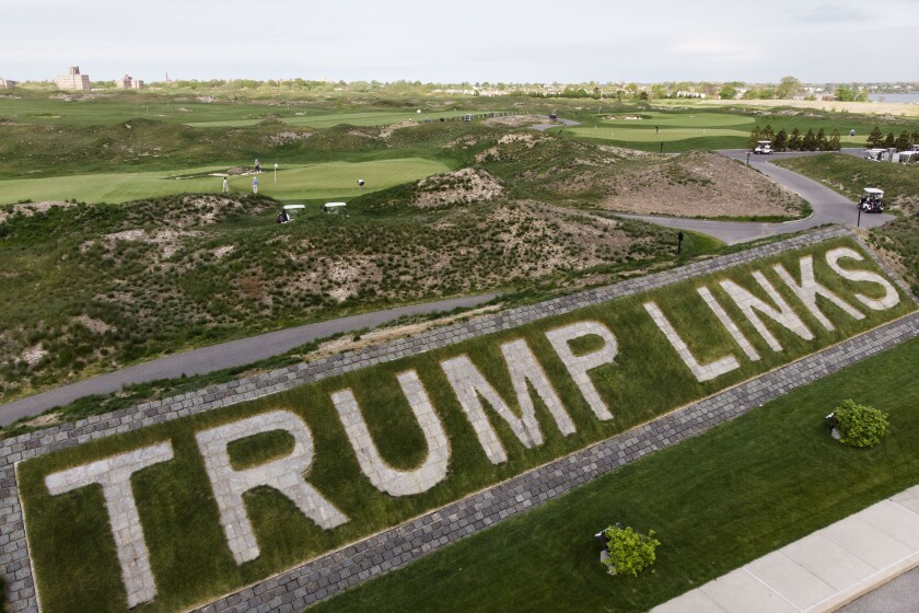 """FILE - Patrons play the links as a giant branding sign is displayed with flagstones at Trump Golf Links at Ferry Point in the Bronx borough of New York on Tuesday, May 4, 2021. The Trump Organization sued New York City on Monday, June 21, 2021 for cancelling its contract to run a golf course in the Bronx earlier this year, a move it called ''politically motivated"""" with no basis in the law that should be reversed. (AP Photo/John Minchillo, File)"""