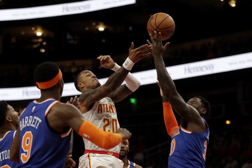 Atlanta Hawks forward John Collins (20) battles New York Knicks forward Julius Randle (30) as he drives to the basket during the first half of an NBA basketball game Wednesday, March 11, 2020, in Atlanta. (AP Photo/John Bazemore)