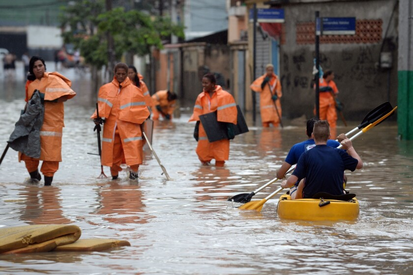 City hall workers walk in a flooded street of a suburb of Rio de Janeiro on Thursday.