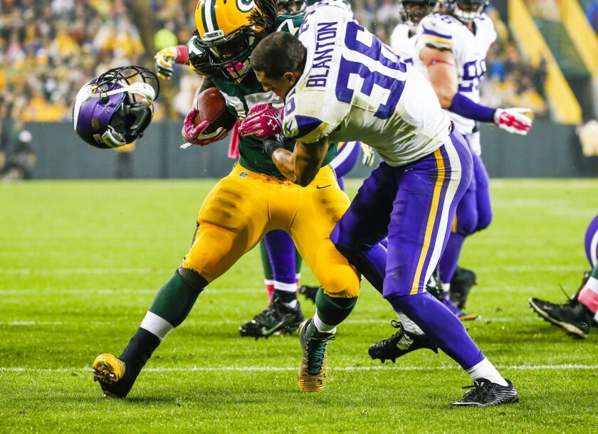 Green Bay Packers player Eddie Lacy, left, knocks the helmet off of Minnesota Vikings defensive player Robert Blanton as he runs for a touchdown.