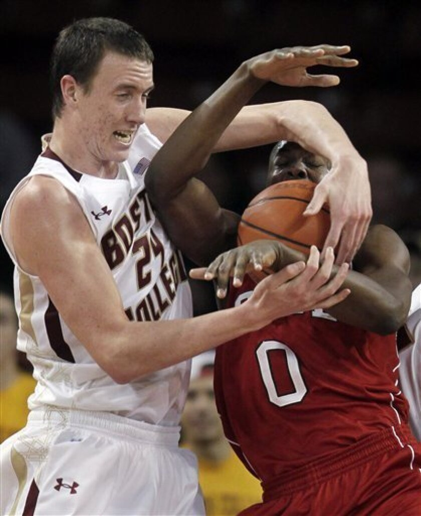 Boston College's Dennis Clifford, left, and North Carolina State's DeShawn Painter, right, grapple for control of the ball during the second half of an NCAA college basketball game in Boston, Wednesday, Feb. 1, 2012. (AP Photo/Steven Senne)