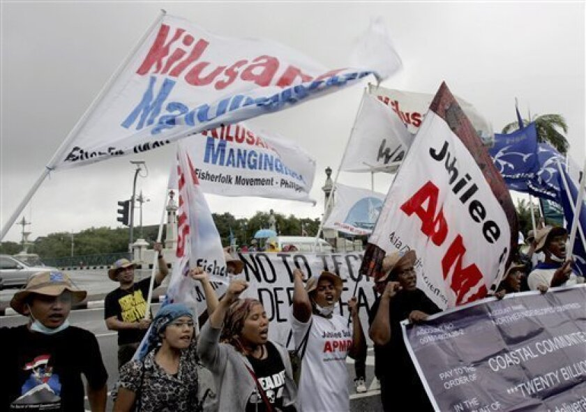 Activists chant slogans and wave flags during a protest outside the U.N. regional office, where delegates are holding talks on climate change Thursday, Oct. 1, 2009 in Bangkok, Thailand. Activists and fishers from Southeast Asia blamed northern countries on the recent severe flooding that was experienced by the Philippines, Vietnam and Cambodia due to massive rains brought by typhoon Ketsana. (AP Photo/Apichart Weerawong)