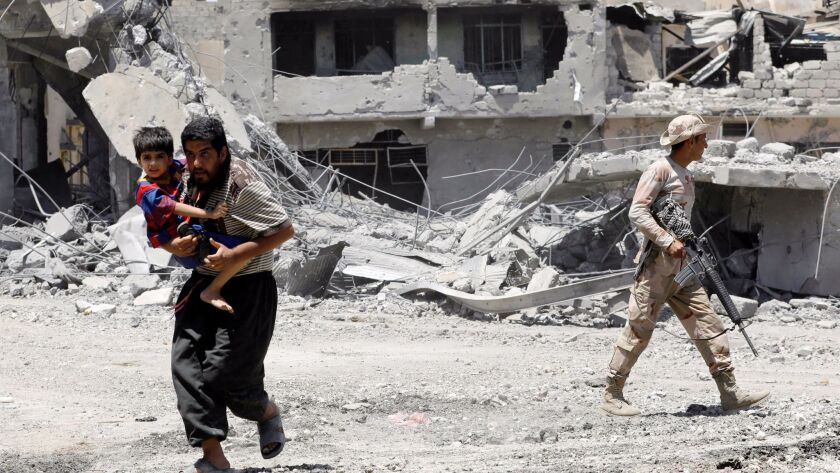 A man carries his child as he runs to a safer place near an Iraqi soldier standing guard in Mosul's