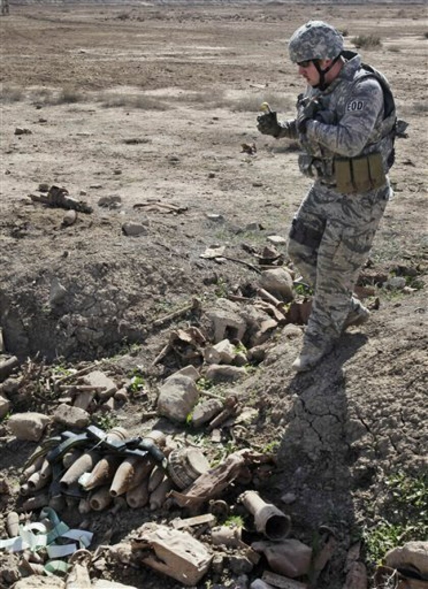 In this Feb. 27, 2010  photo, senior Airman Bryan Bell, 22, Erie, Pa., part of a U.S. Air Force Explosive Ordnance Disposal (EOD) team attached to the U.S. Army's 4th Brigade 1st Armored Division, carries explosives he will use to detonate a weapons cache that was turned over to them by an Iraqi in