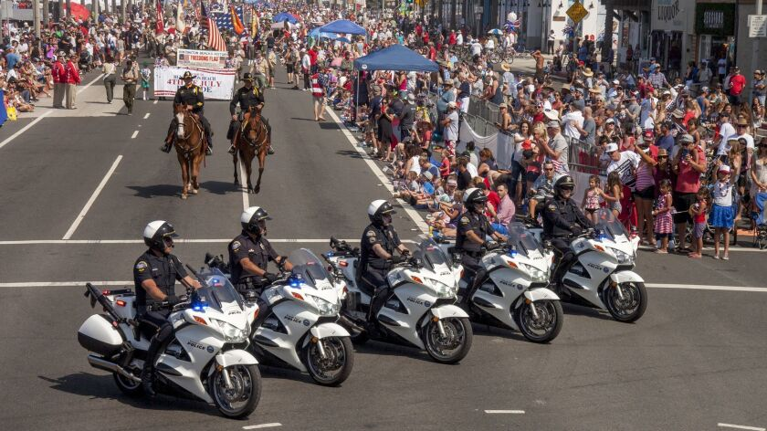 The Huntington Beach Police Department says it received 5,645 alarm-related calls in 2017, of which 3,816 were false alarms and 30 were for confirmed crimes. Here, motorcycle officers are pictured riding in the city's 2017 Fourth of July Parade.