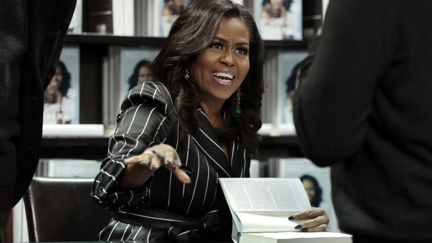 """Michelle Obama signs copies of her memoir """"Becoming"""" in New York on Nov. 30, 2018."""