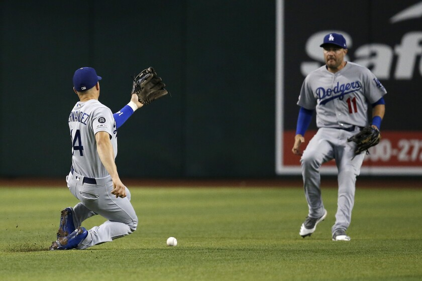 A pop fly hit by Arizona's Eduardo Escobar between Dodgers second baseman Enrique Hernandez, left, and center fielder A.J. Pollock for a single during the fourth inning of Thursday's loss.