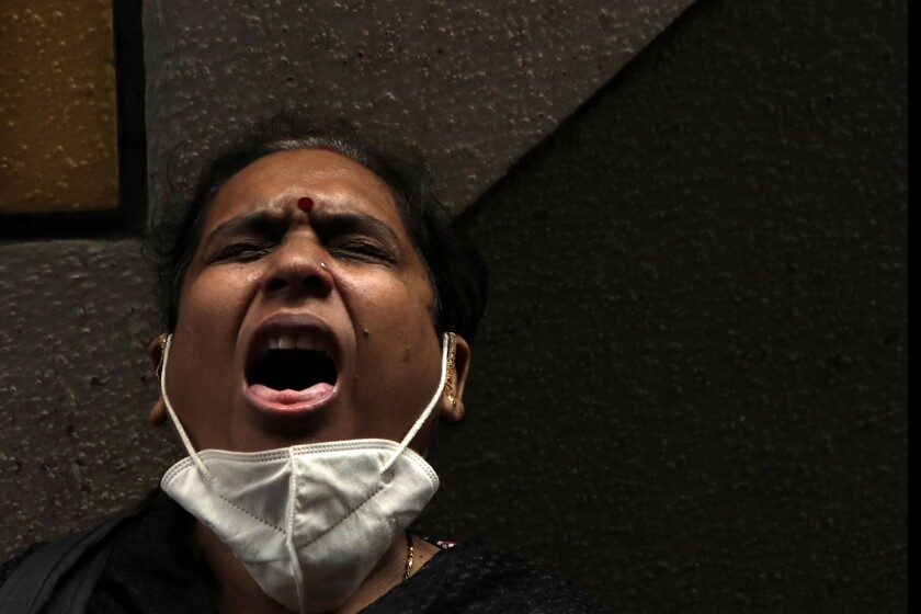 A Blind woman reacts after a health worker takes a swab sample for COVID-19 test at medical camp in Mumbai, India, Saturday, July 25, 2020. India is the third hardest-hit country by the pandemic in the world after the United States and Brazil. (AP Photo/Rajanish Kakade)