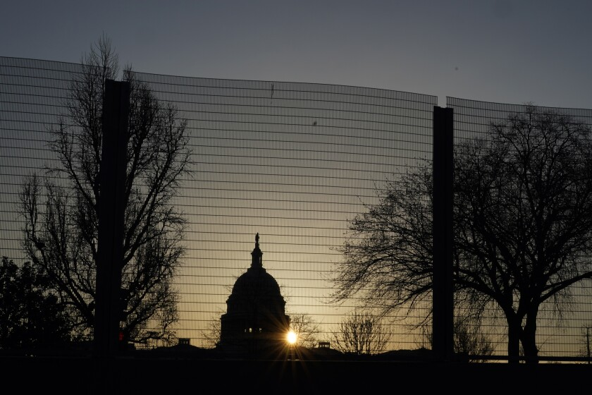The sun rises behind the Capitol dome.