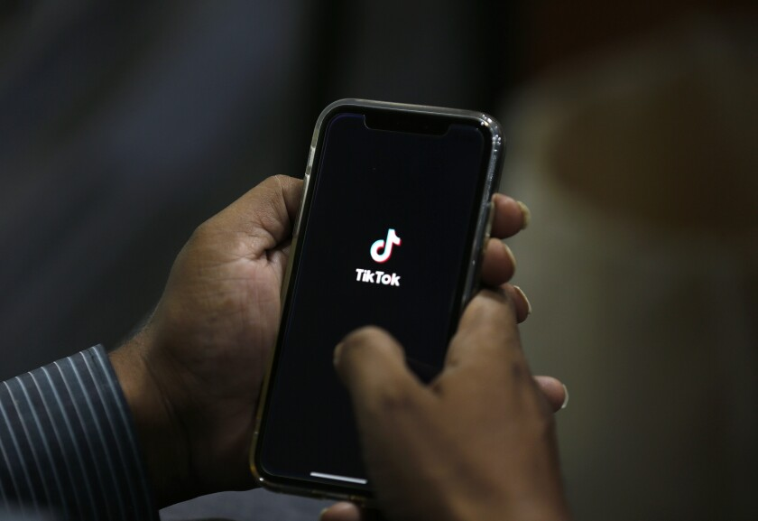 A pair of hands holds a cellphone with the TikTok logo on the screen.