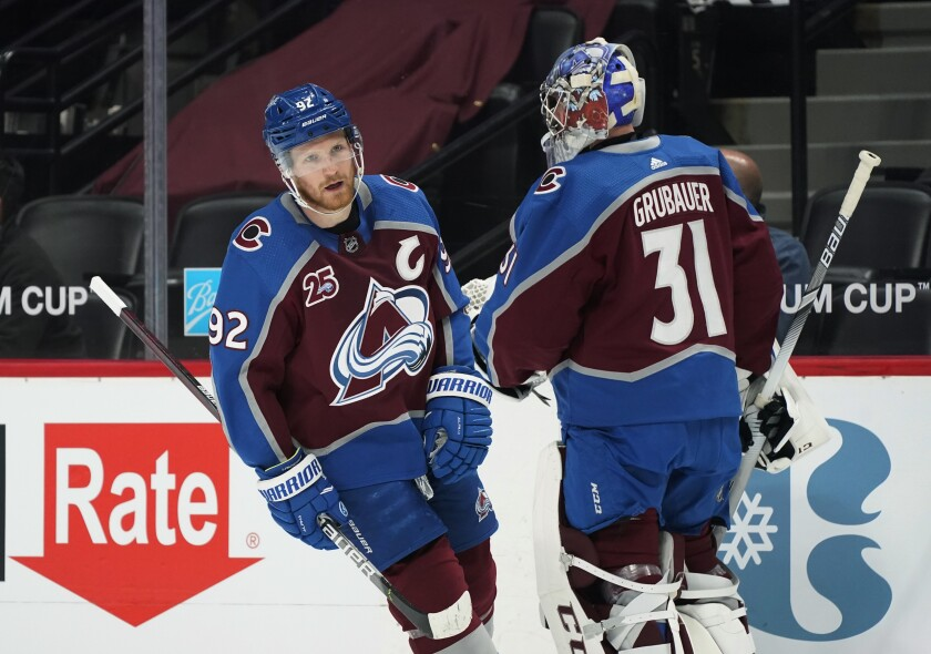 """FILE - In this April 30, 2021, file photo, Colorado Avalanche left wing Gabriel Landeskog (92) skates past goaltender Philipp Grubauer during the first period of the team's NHL hockey game against the San Jose Sharks in Denver. Avalanche general manager Joe Sakic still is not sure the team will be able to bring back Landeskog and Grubauer.""""I don't know,"""" Sakic said. """"We're hopeful we can come to terms, as well, and have them signed and to be part of us."""" (AP Photo/David Zalubowski, File)"""