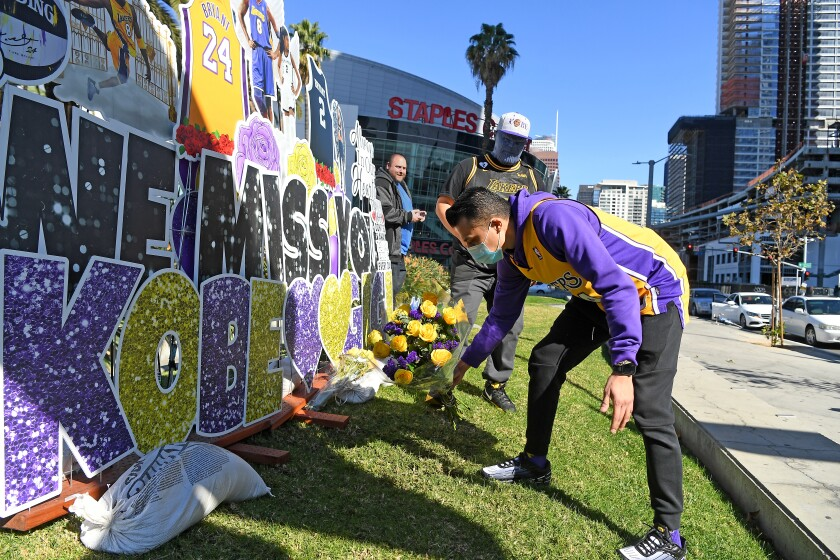 Nestor Magana lays flowers in front of a Kobe Bryant mural in downtown L.A. on the one-year anniversary of Bryant's death.