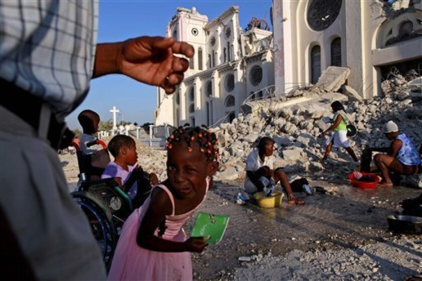 Children play around women washing clothes with water spilled from a broken tube outside the National Cathedral in Port-au-Prince, Sunday, Feb. 7, 2010. A 7.0-magnitude earthquake hit Haiti on Jan. 12, killing and injuring thousands. (AP Photo/Rodrigo Abd)
