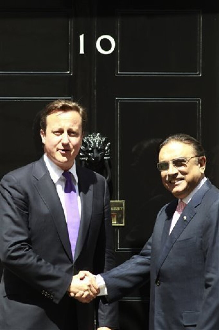 Britain's Prime Minister David Cameron, left, poses for pictures with Pakistan's President Asif Ali Zardari as he welcomes him outside his official residence at 10 Downing street Street in London, prior to their meeting, Friday, July 1, 2011, (AP Photo/Lefteris Pitarakis)