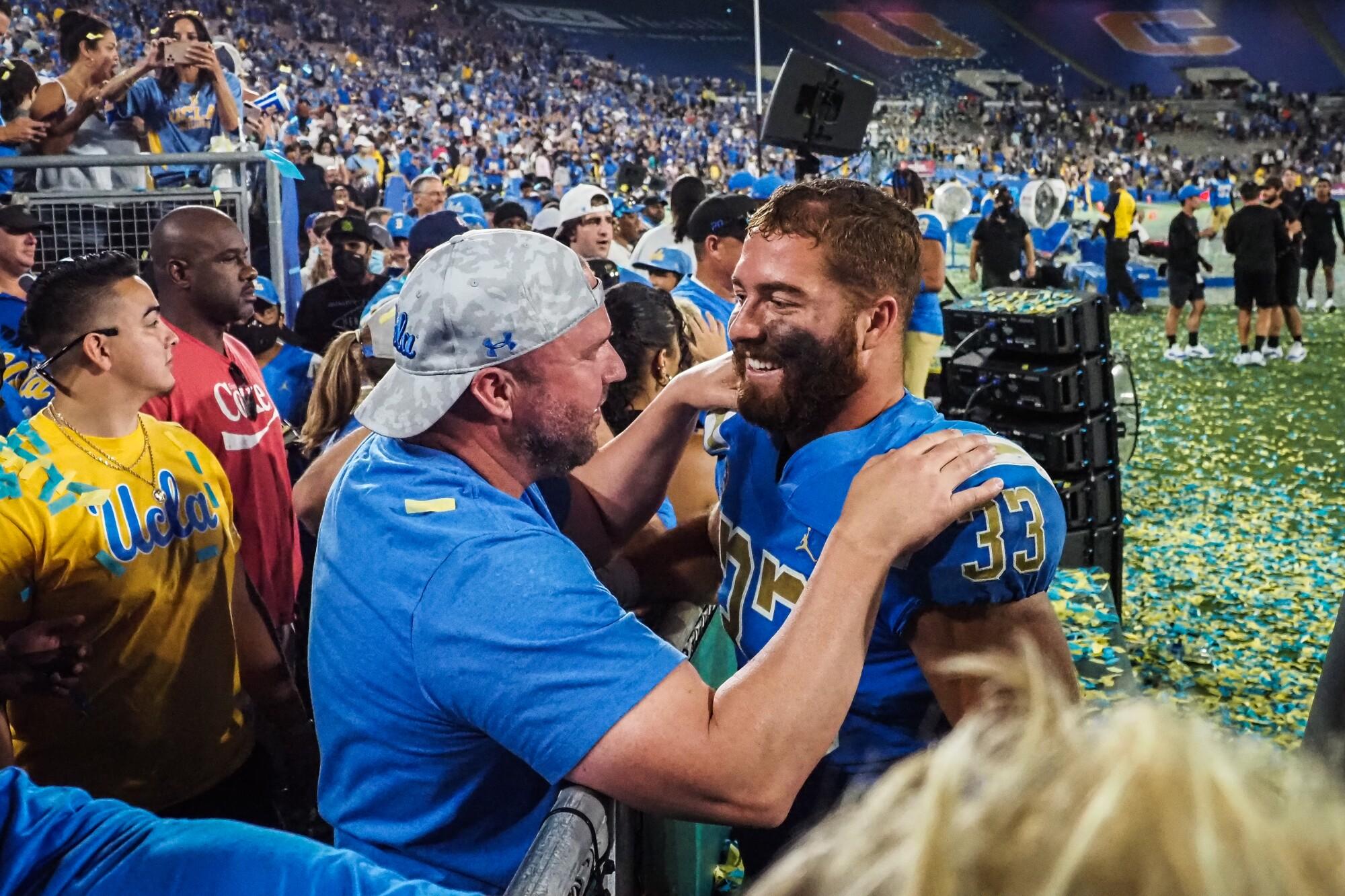 David Calvert hugs his son, UCLA linebacker Bo Calvert, after the Bruins' win over LSU.