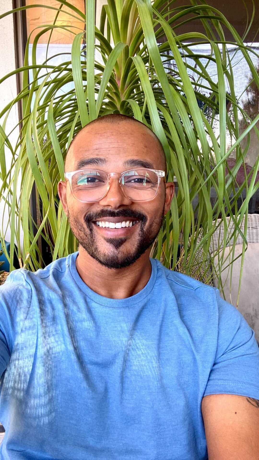 A smiling man wearing clear-framed glasses and a blue T-shirt, in front of a hanging plant.