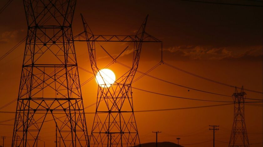 ADELANTO, CALIF. - AUG. 30, 2017. The sun sets behind power lines at the end of a scorching hot da