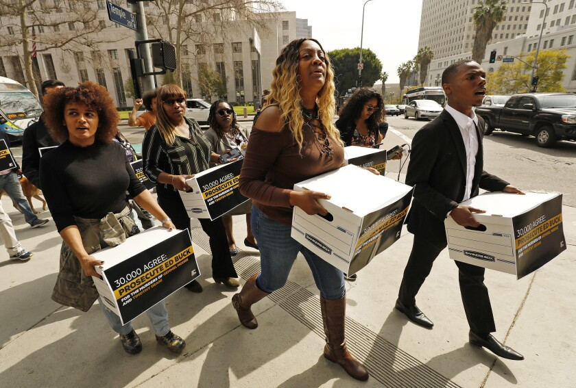 People carry boxes of petitions across a street